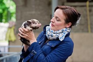 Ella McSweney ith Kune Kune piglet - jennifer o'sullivan
